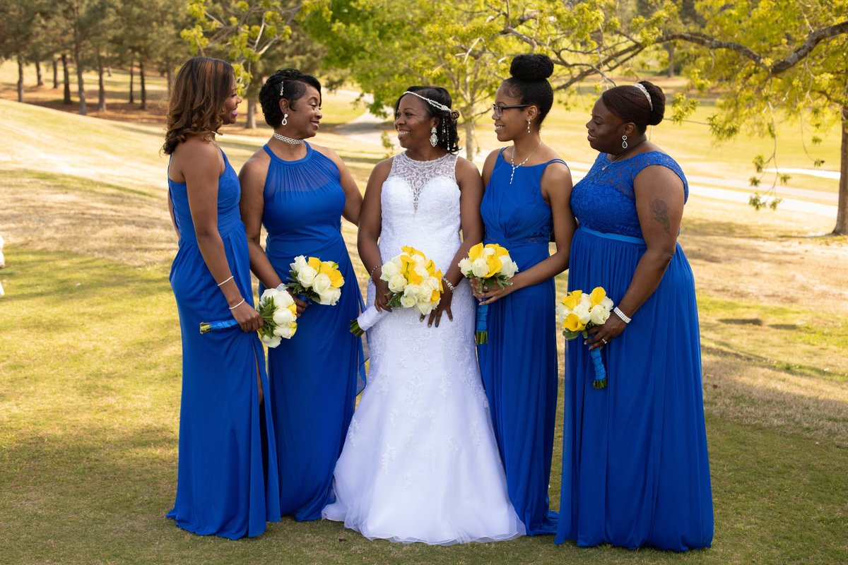 Black bridal party laughing on golf course
