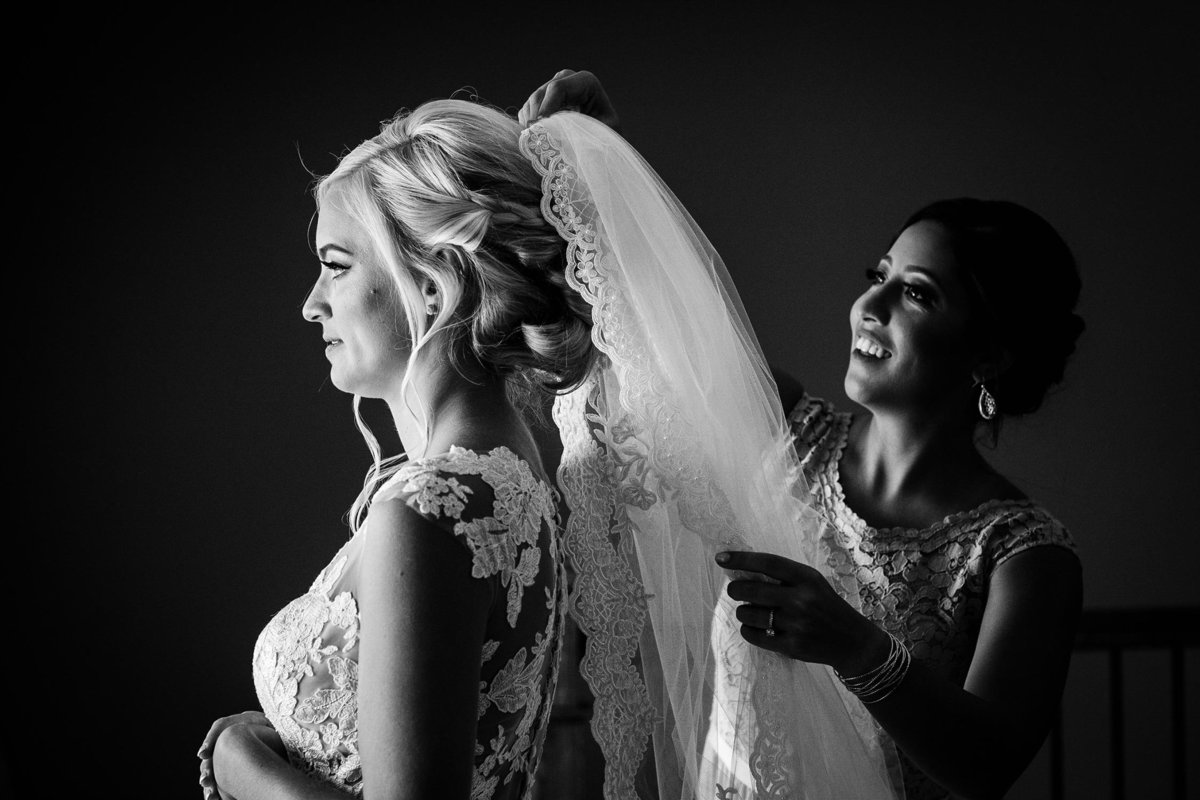 A bridesmaid adjusts the bride's veil before a Silver Lake Country Club wedding.