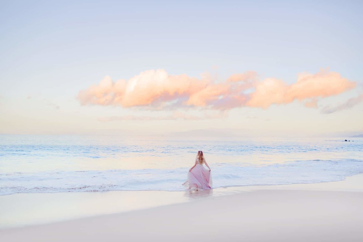 Bride holding her dress on the beach in Maui at sunrise