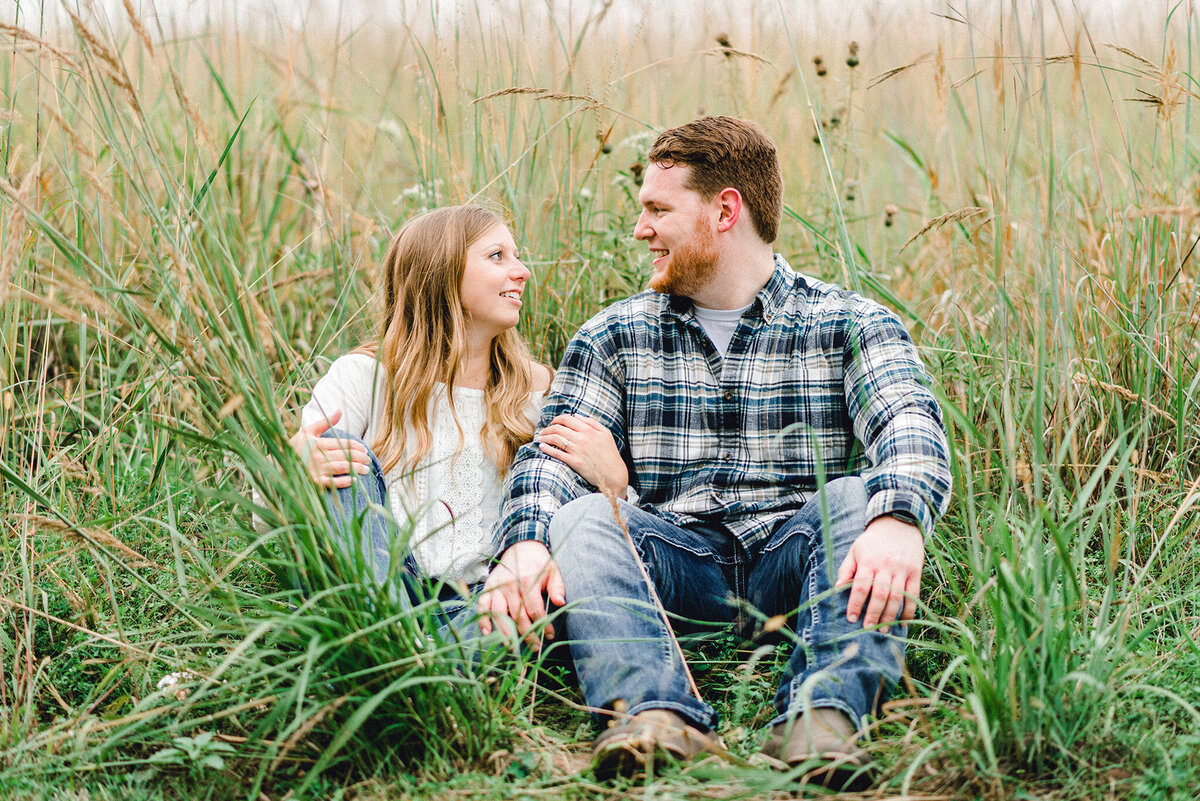 couple sits in tall grass at chalco hills