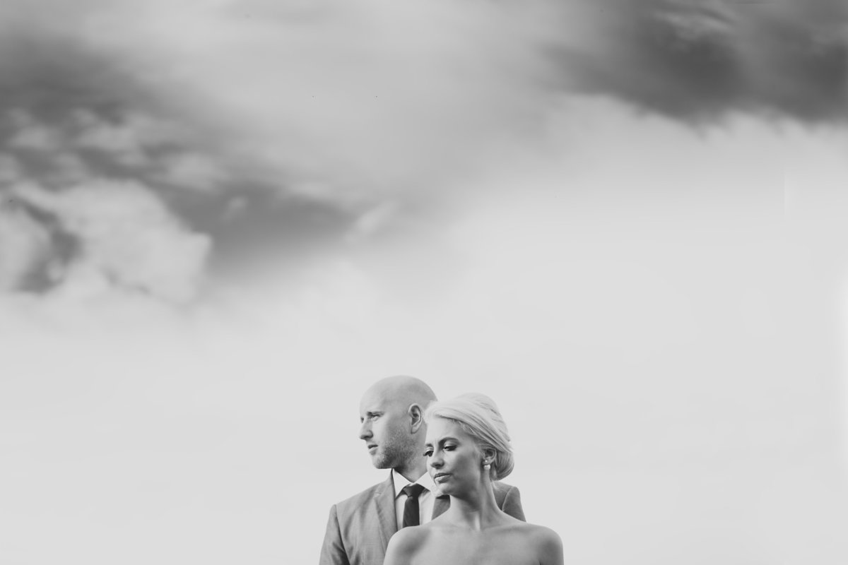 creative wedding photo of couple against a cloudy sky