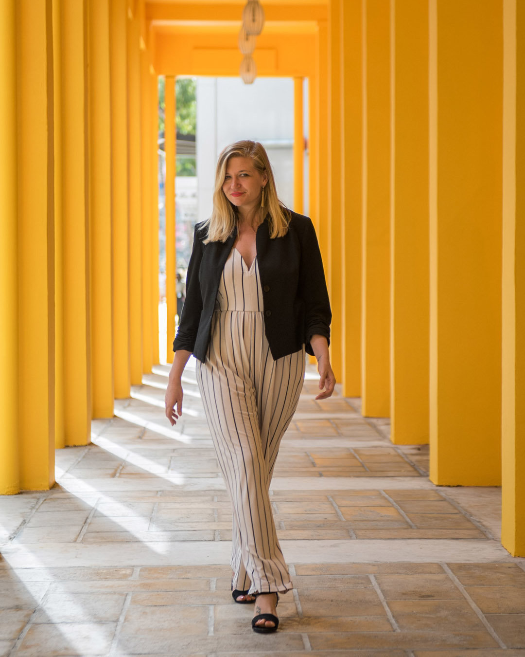 woman walking along yellow pillars