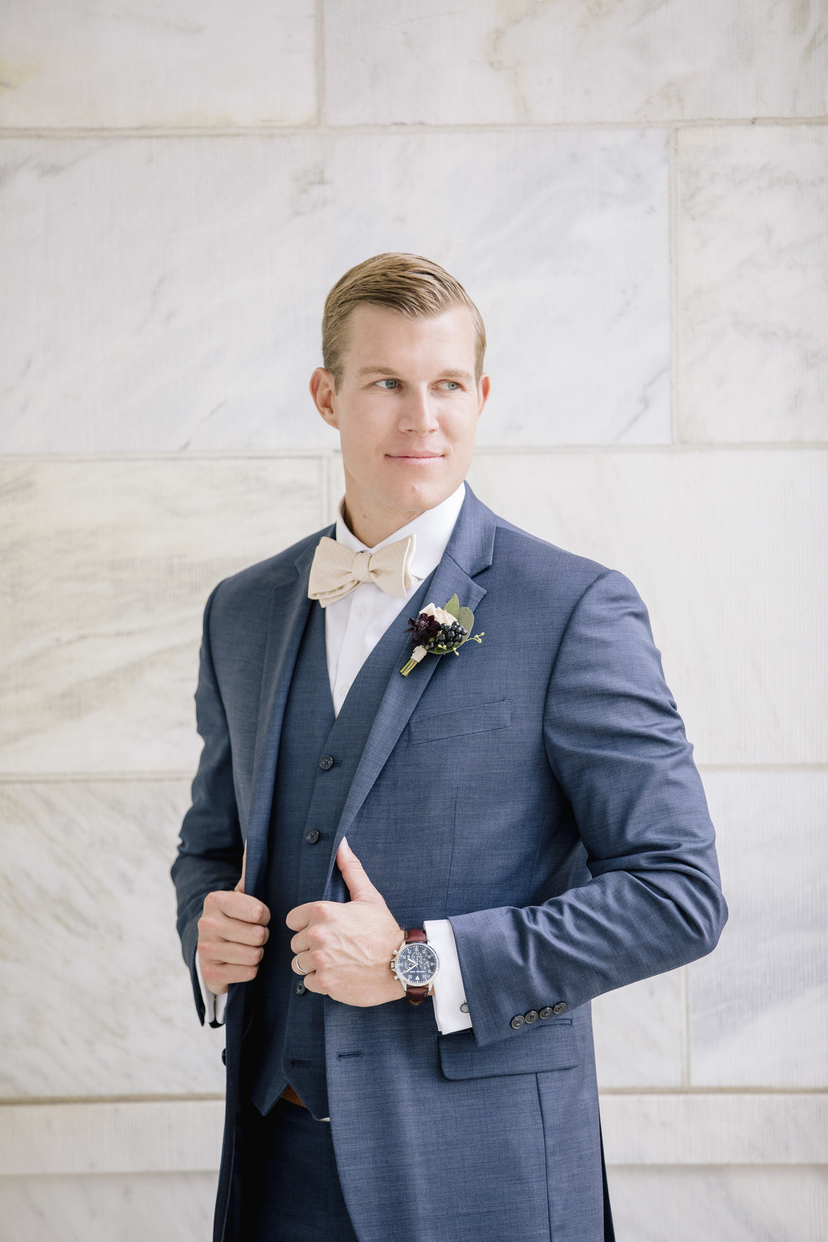 groom in front of white marble in asbury park