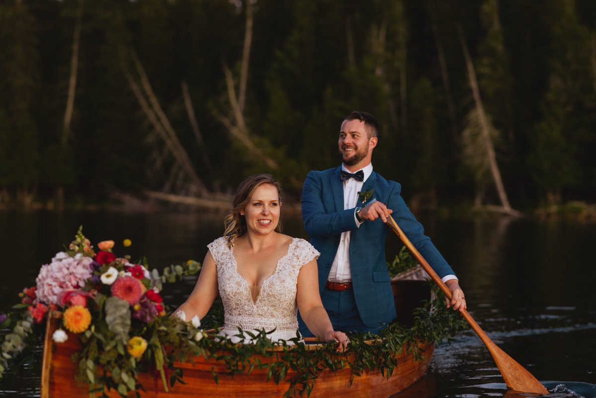 bride and groom canoeing at sunset on a lake