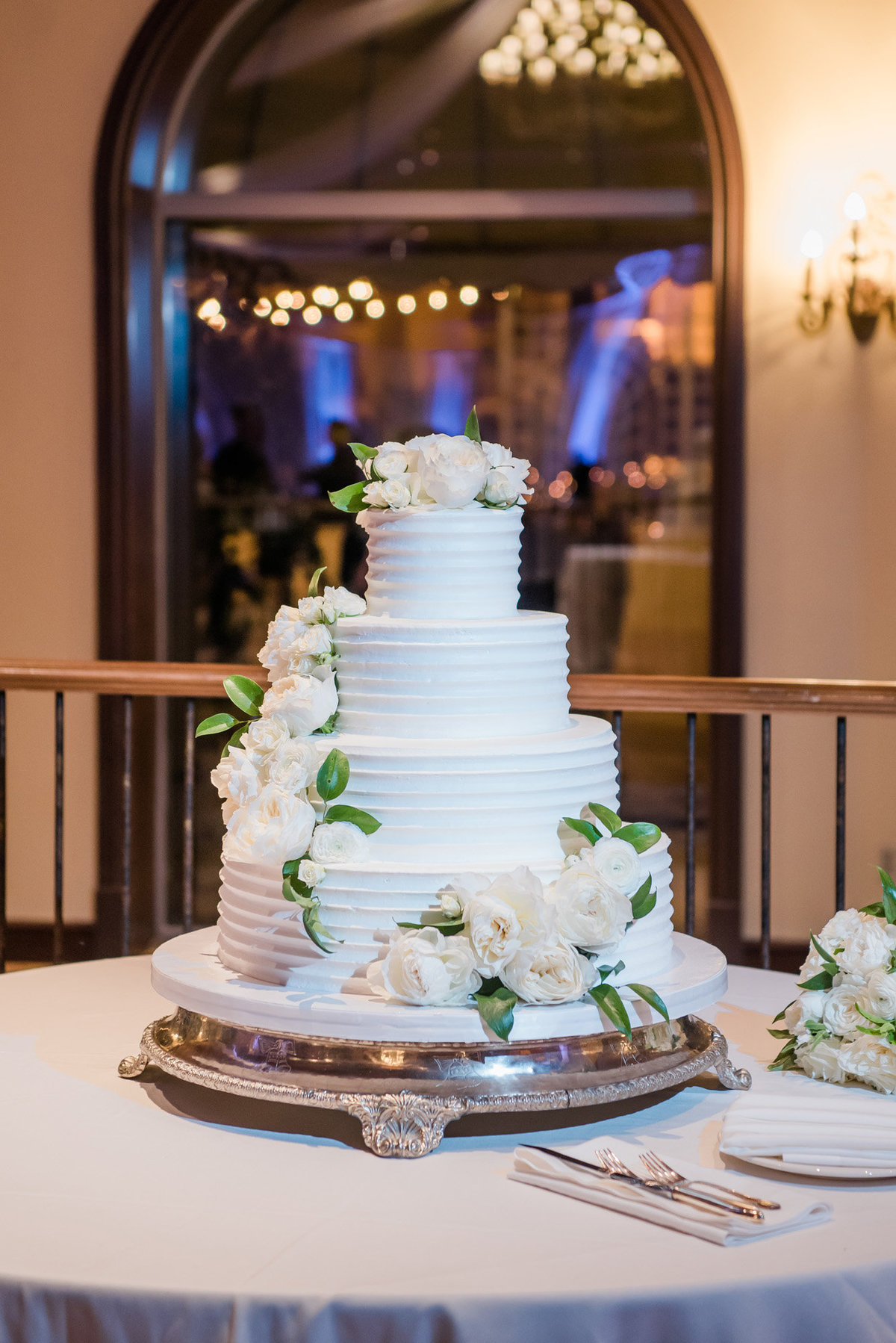 a simple white wedding cake with white flowers and a touch of greenery at the JW Marriott Resort and Spa in Las Vegas