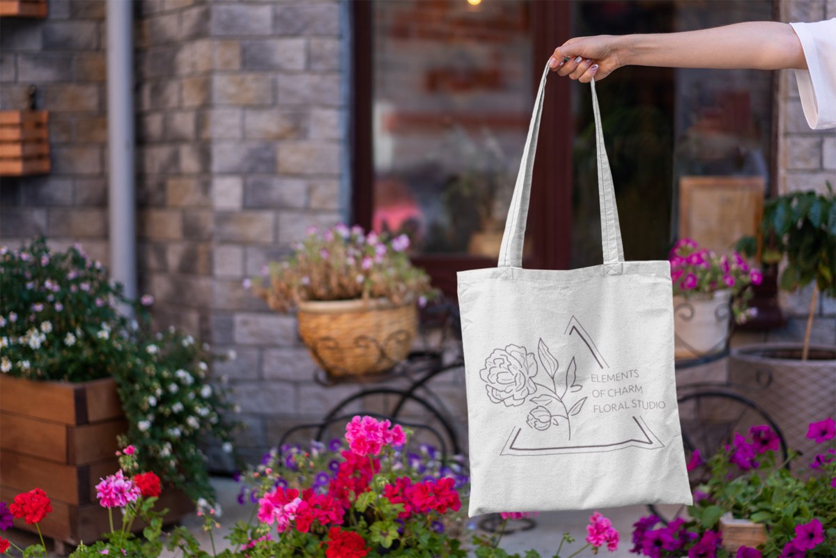 mockup-featuring-a-woman-s-hand-holding-a-tote-bag-by-some-flower-pots-3137-el1