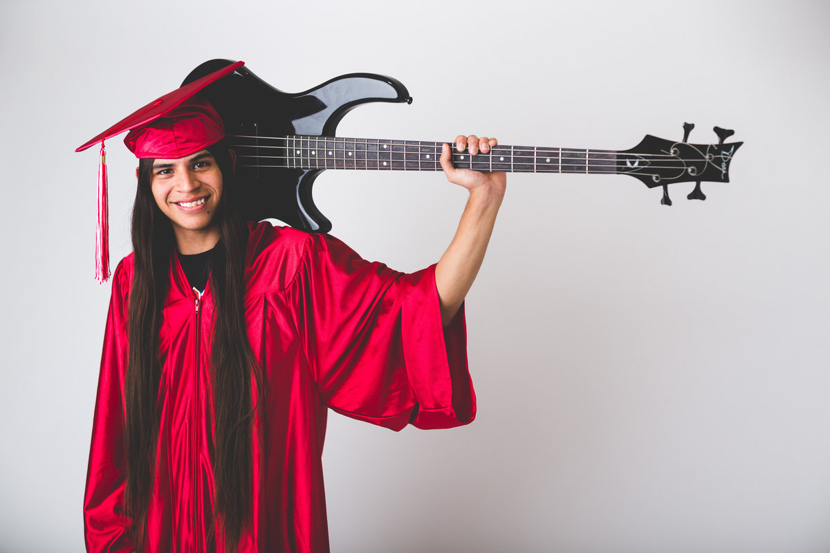 high school senior session of guy in cap and  gown with guitar by San Antonio senior photographer