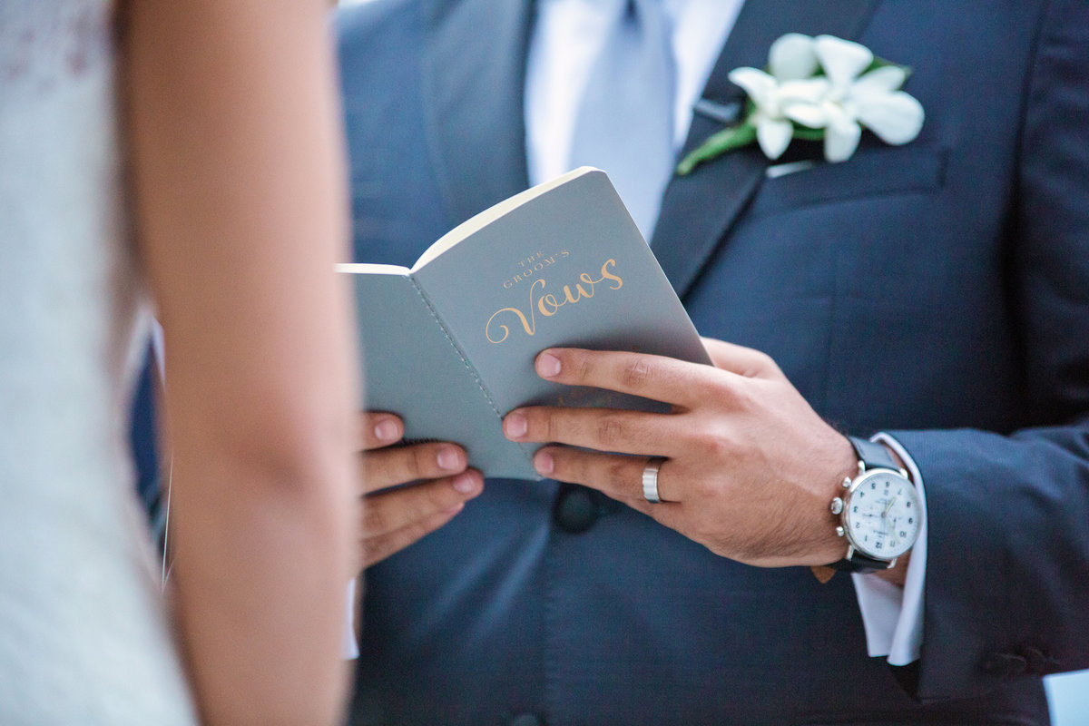 groom holding a notebook while reading his vows at Harbor Club at Prime