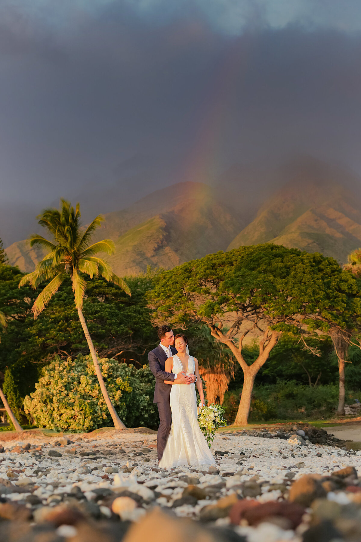 Bride and groom posing in front of Olowalu Plantation House with rainbow in the background
