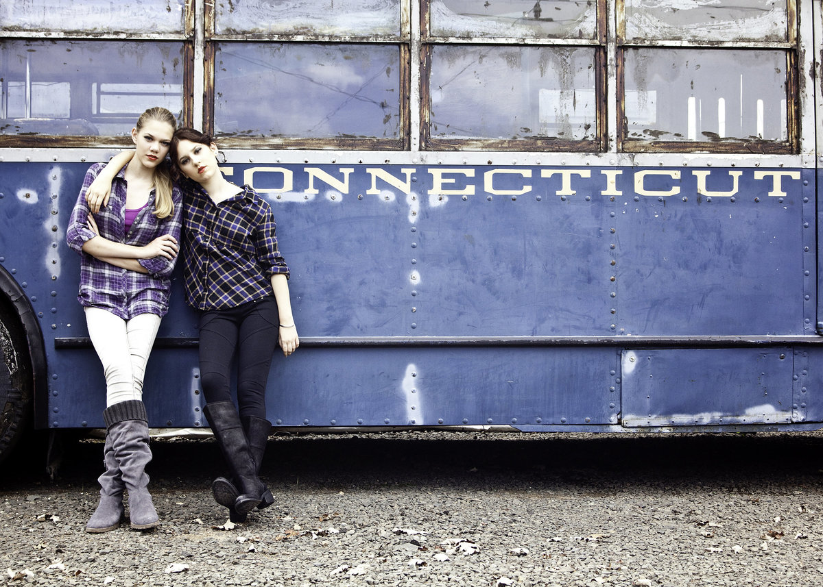 Two high school students captured in front of a bus