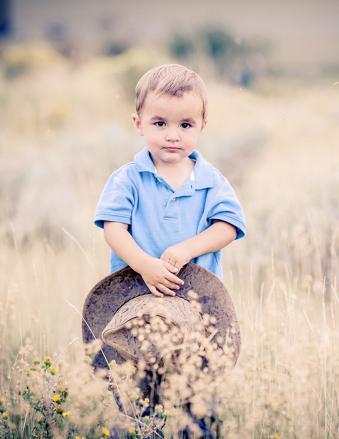 blond haired boy. little boy holding a hat in field of grass near sunrise, family pictures, located in billings montana.