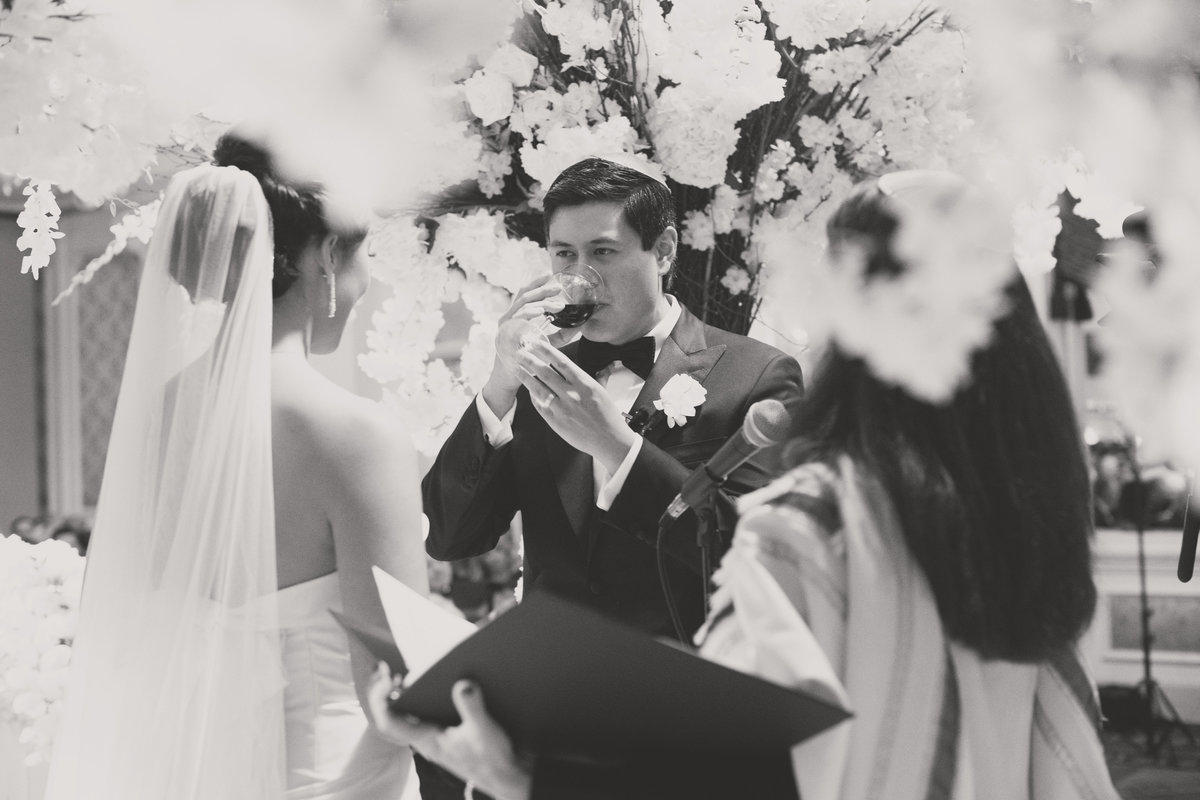 black and white photo of groom drinking from the glass of wine during wine ceremony for wedding at The Garden City Hotel