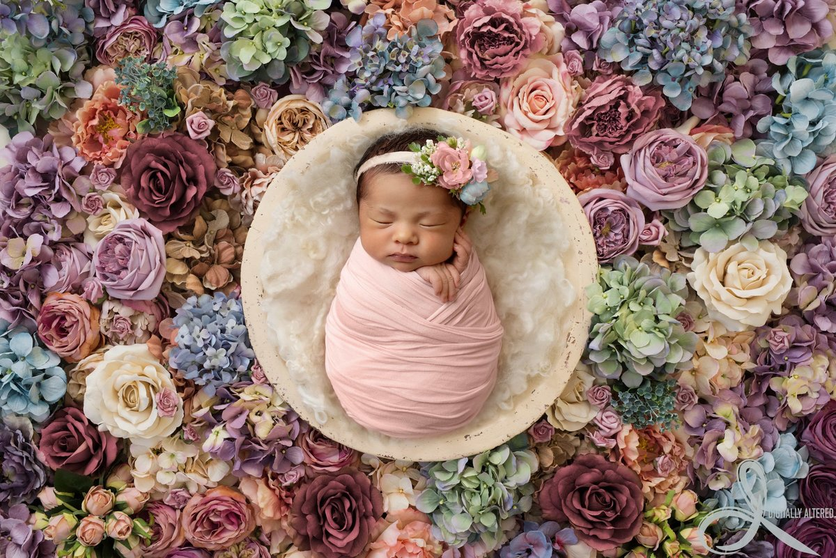 Baby girl surrounded by flowers