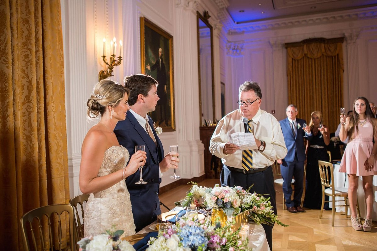 Bride and Groom stand as they accept their toast