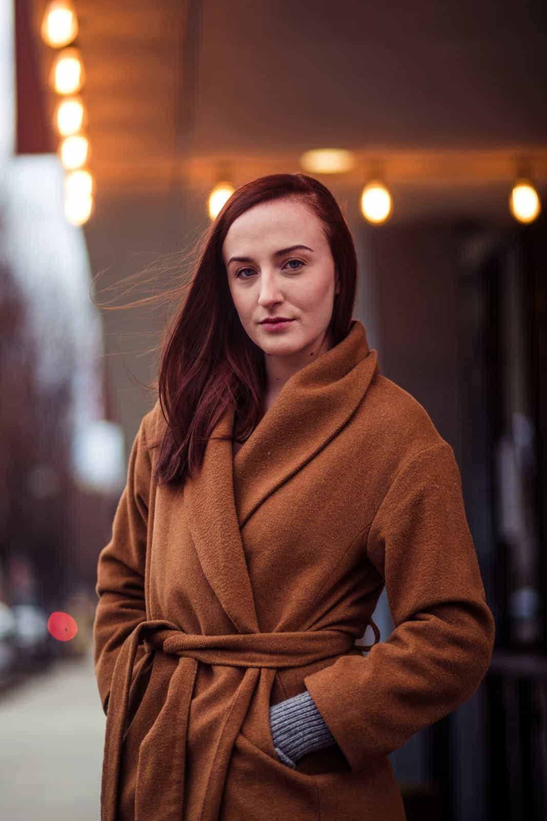redhead girl stands in West Midtown with cashmere coat