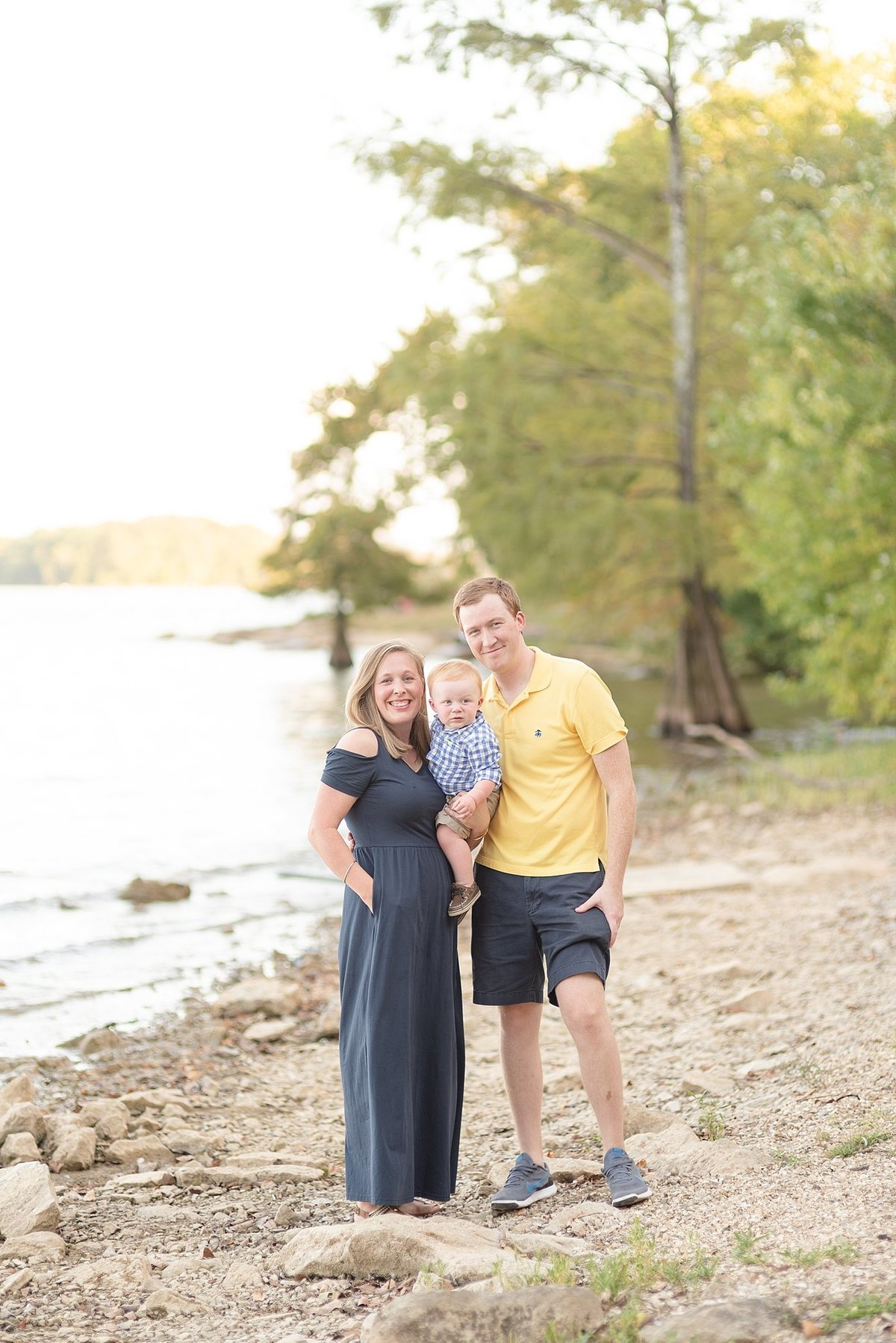 Family of three standing alongside a lakeshore in Nashville, TN for golden hour family portraits by Dolly DeLong Photography