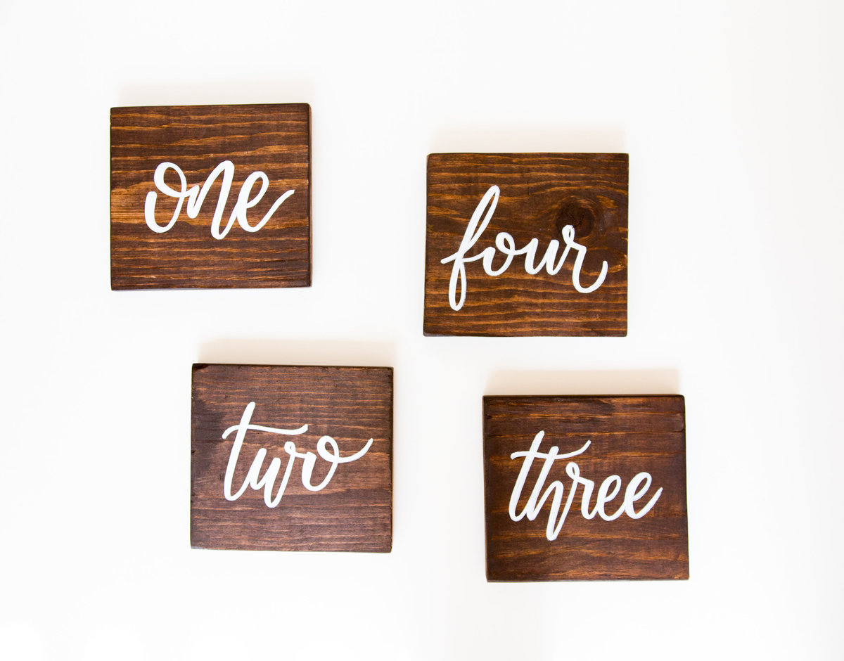 wood table numbers with white calligraphy for weddings or events through Hue + FA Rental