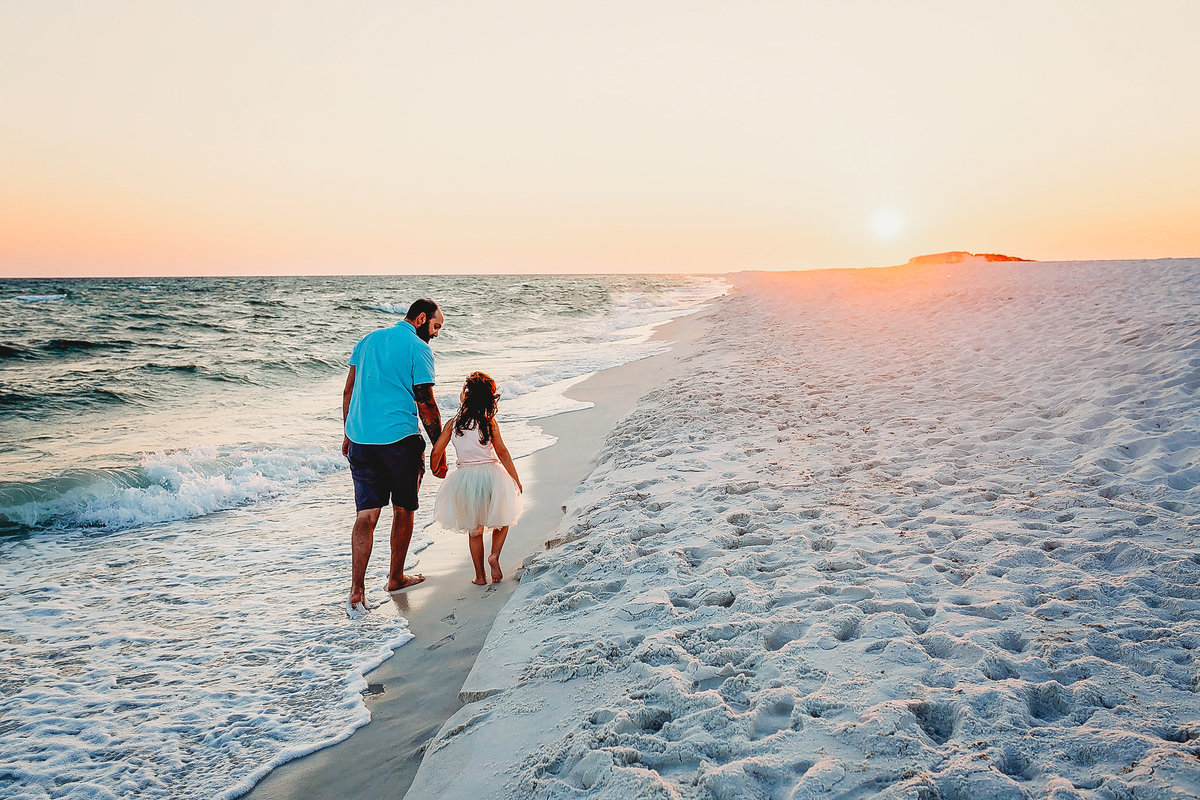 Father and Daughter walk down beach, at sunset