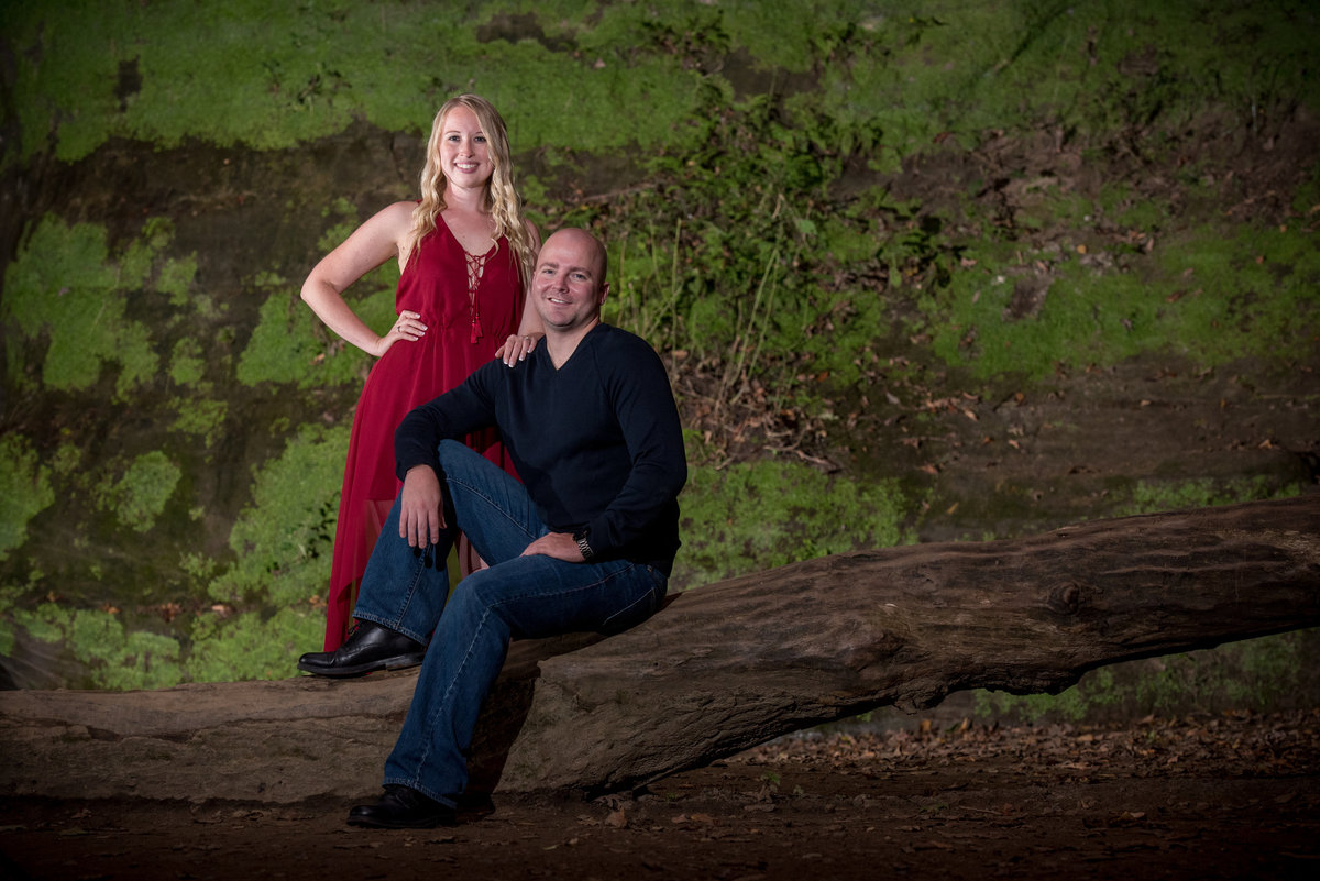 Red dressed bride and her groom pose on a log against a green moss covered wall  of a waterfall at staved rock state park