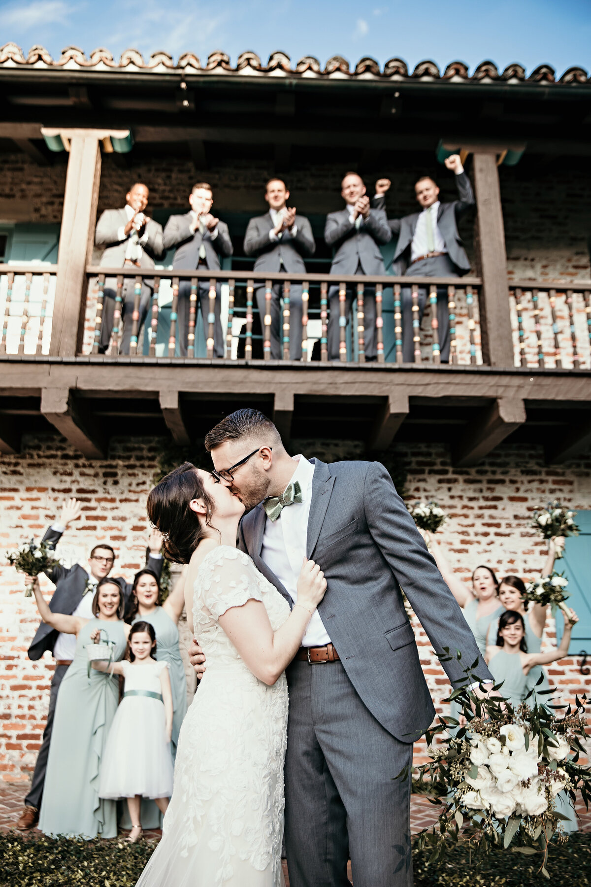 A picture of a bridal couple kissing in front of their vintage wedding venue as their wedding party stands behind them clapping and cheering them on