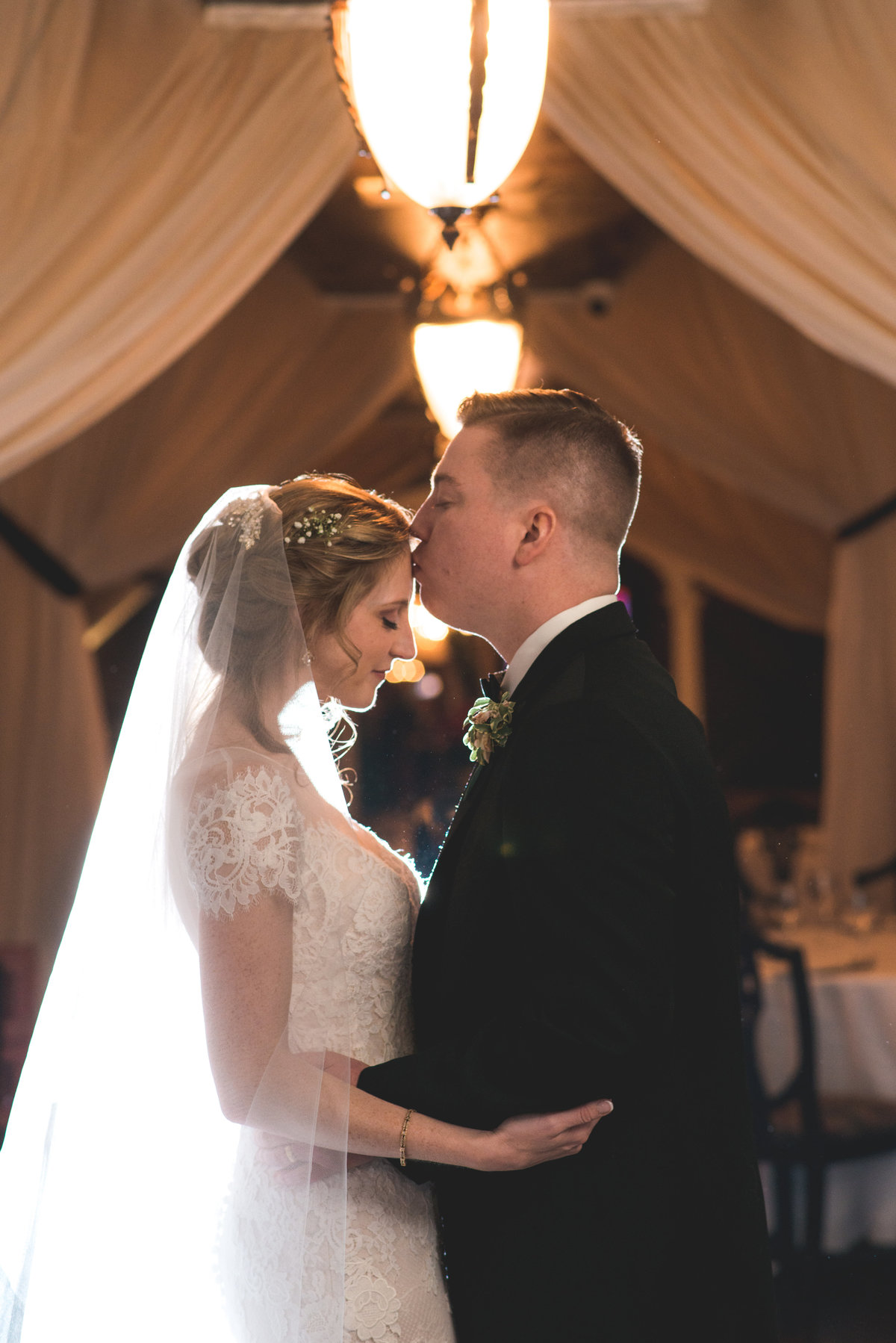 photo of groom kissing bride on the forehead from wedding at The Carltun
