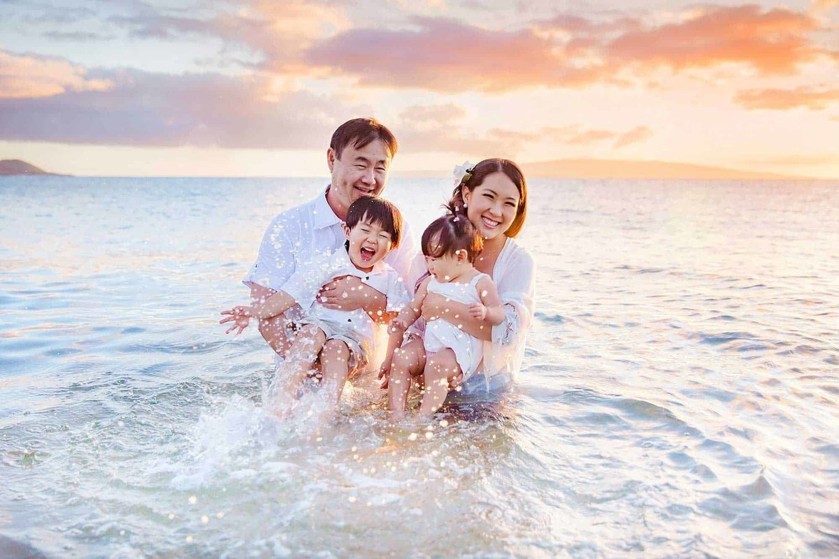 Young family splashes in the water during their Maui family photography session