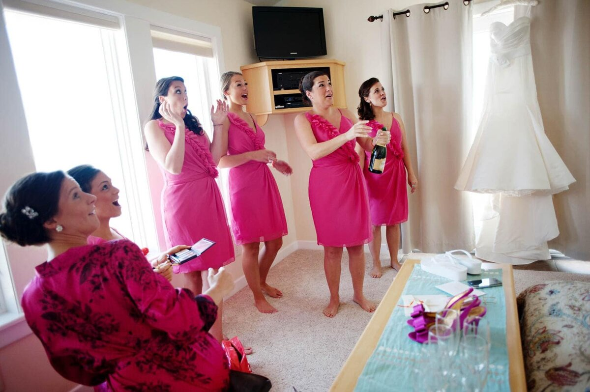 bridesmaids in colorful pink dresses look in surprise as they pop the cork from champagne
