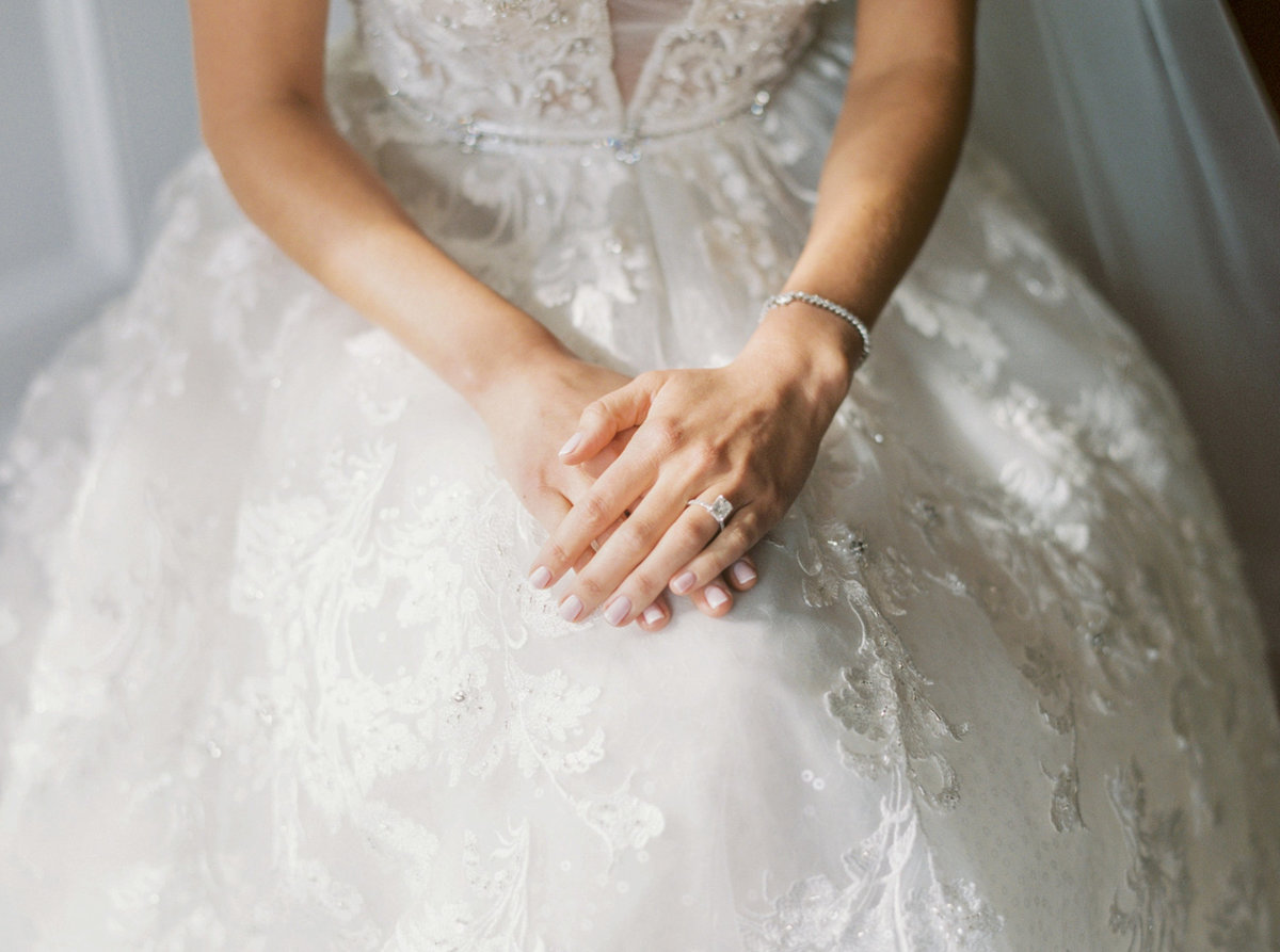 bride sitting with her hands folded over each other showing her engagement ring and wedding gown