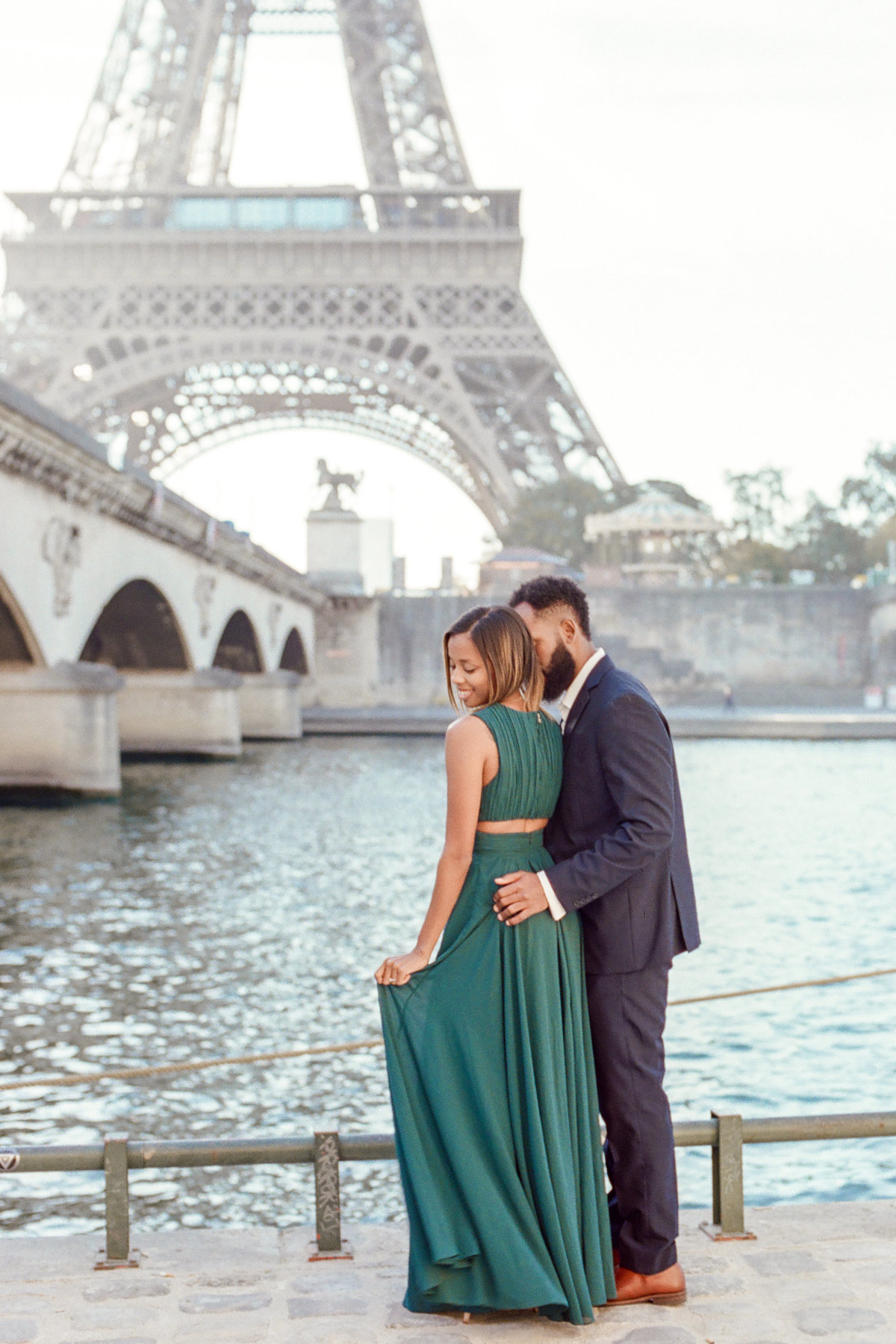 couple standing in front of seine river with eiffel tower in background