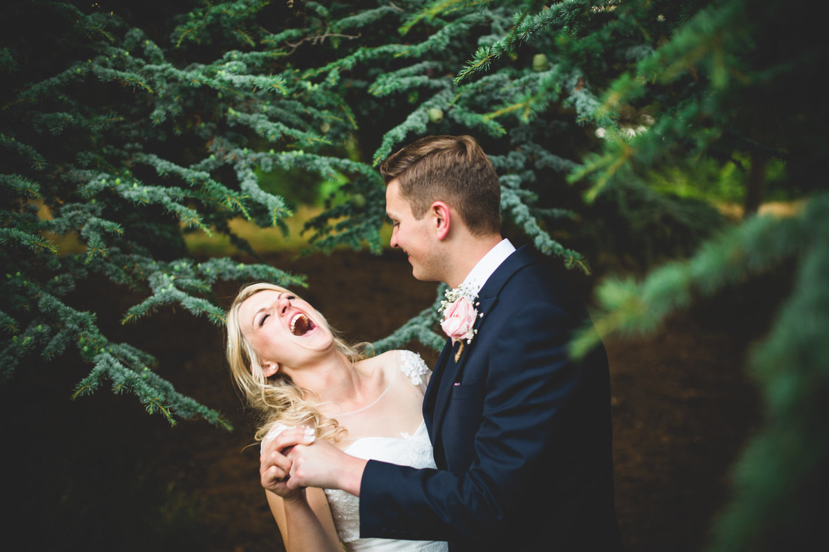funny wedding photo of bride and groom laughing with each other by a fir tree