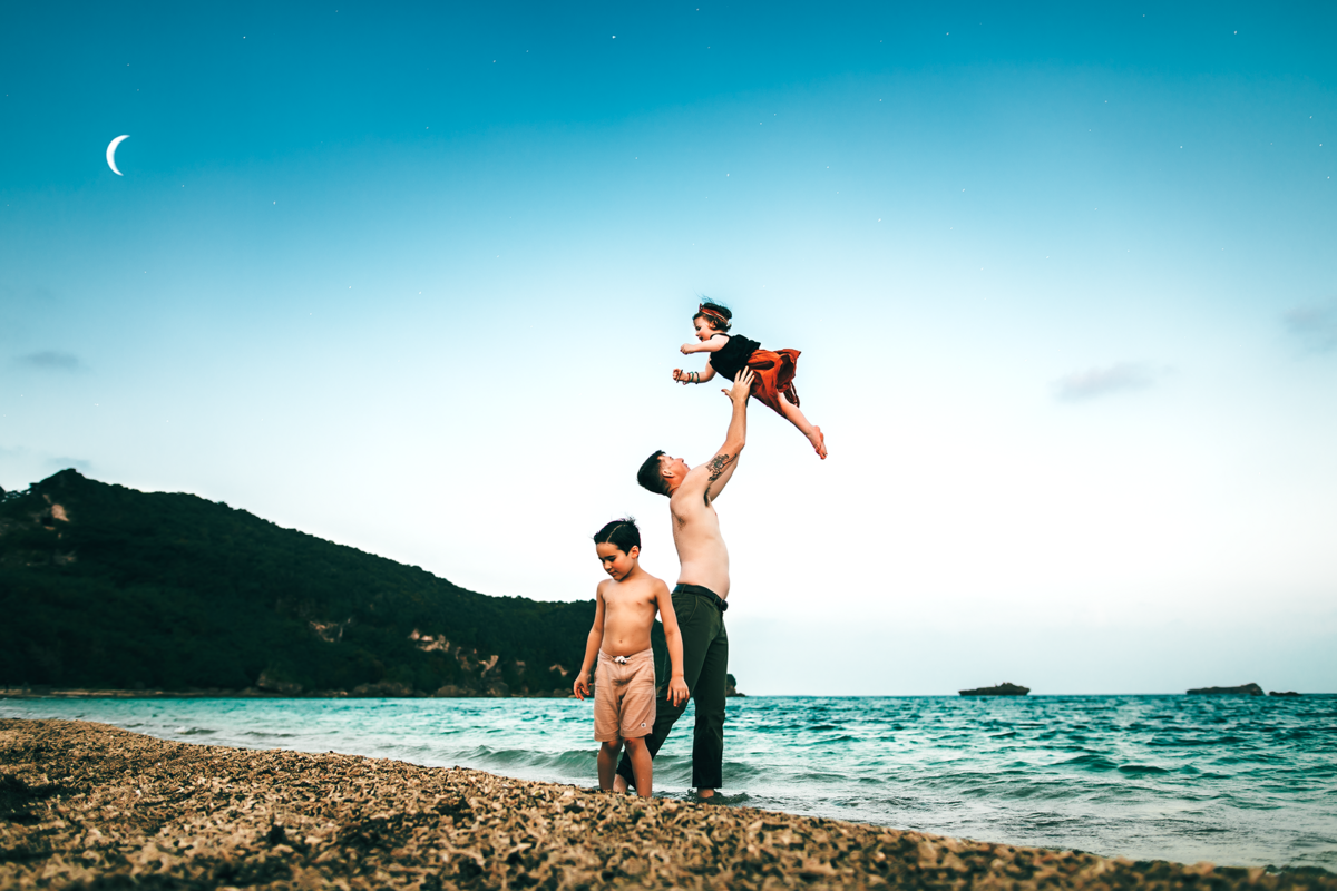 Okinawa Family Photographer, family playing on the beach and dad throwing daughter in the air