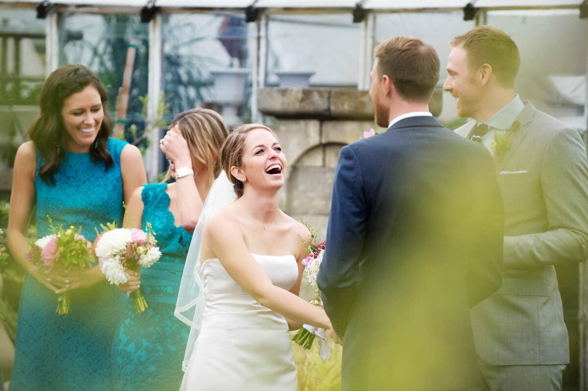 a bride and bridesmaids laugh during a wedding ceremony at castaway pdx