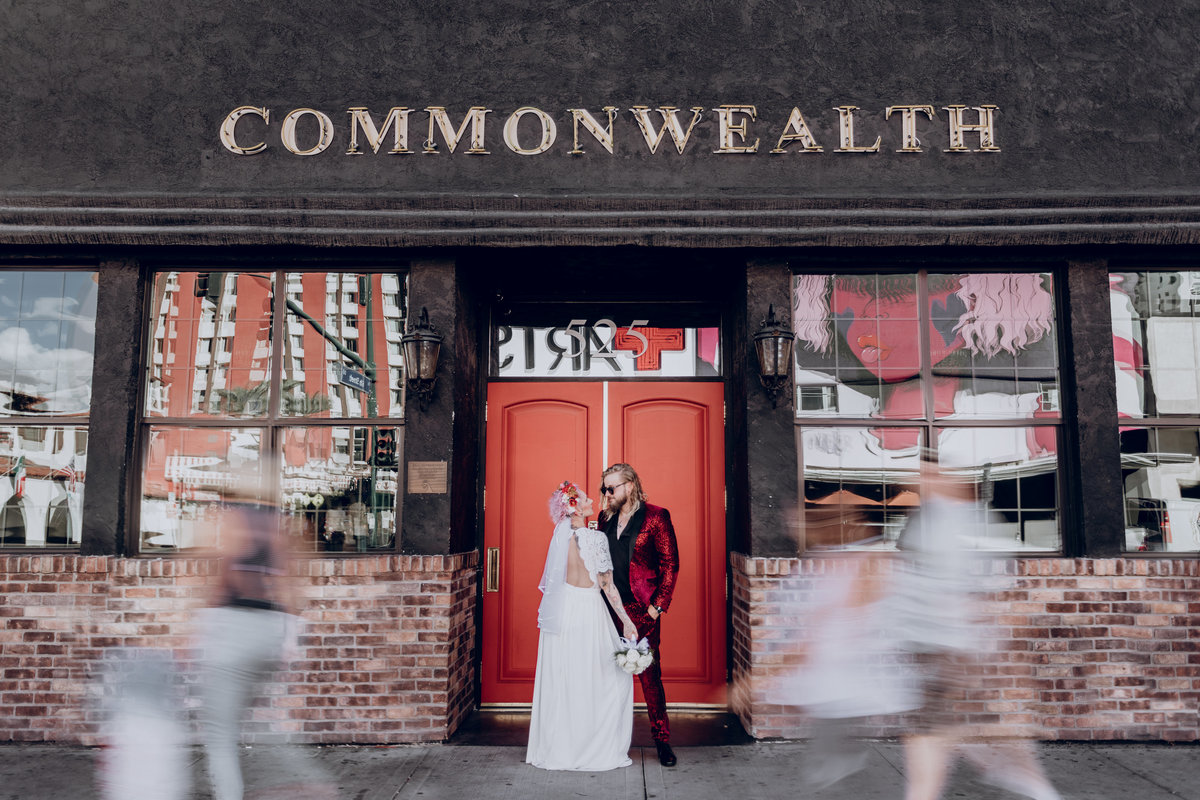Reno elopement photographers couple poses in front of red door