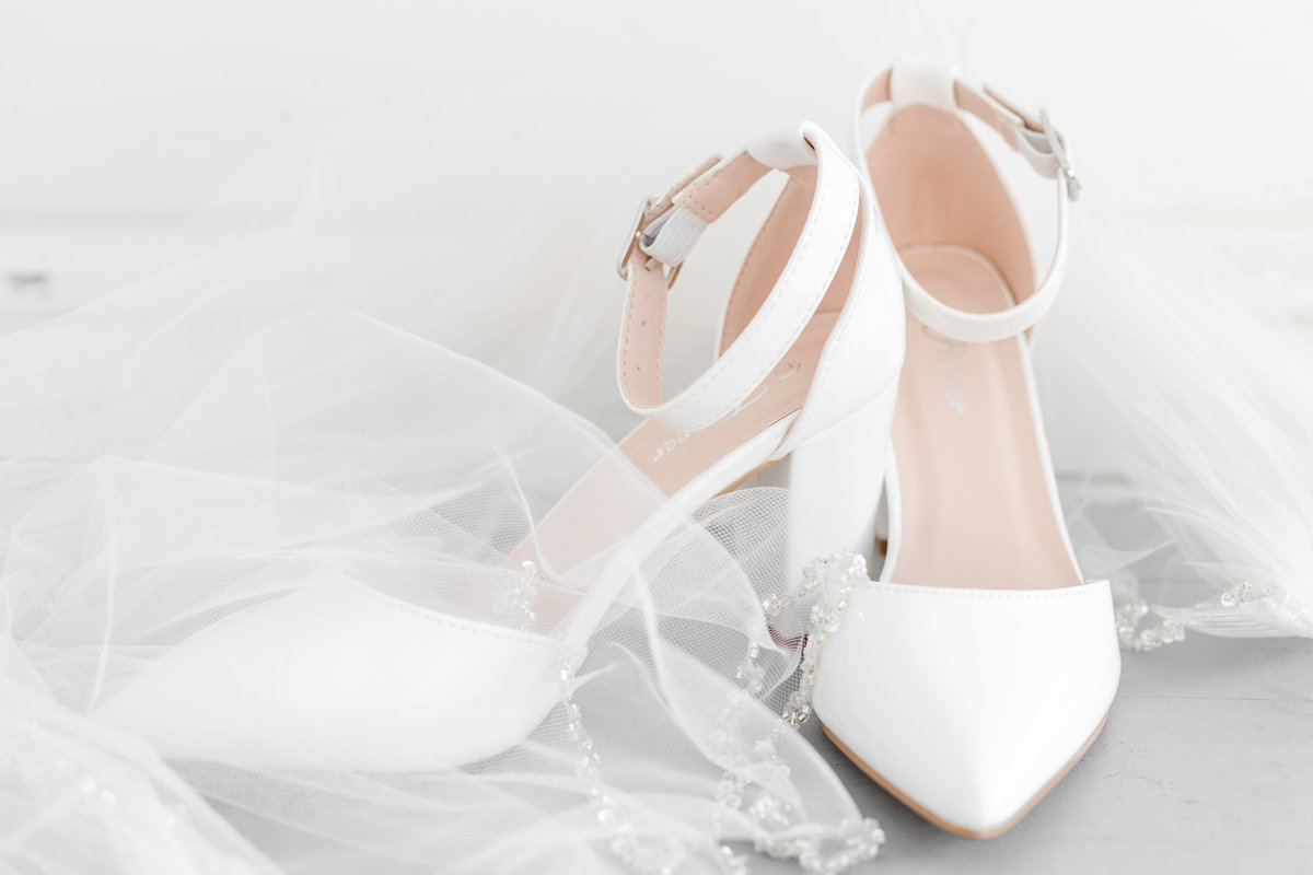 A pair of white heels and a veil