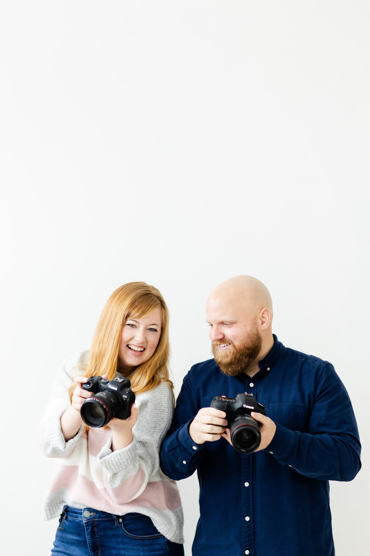 husband and wife wedding photographers posing with cameras for branding shoot
