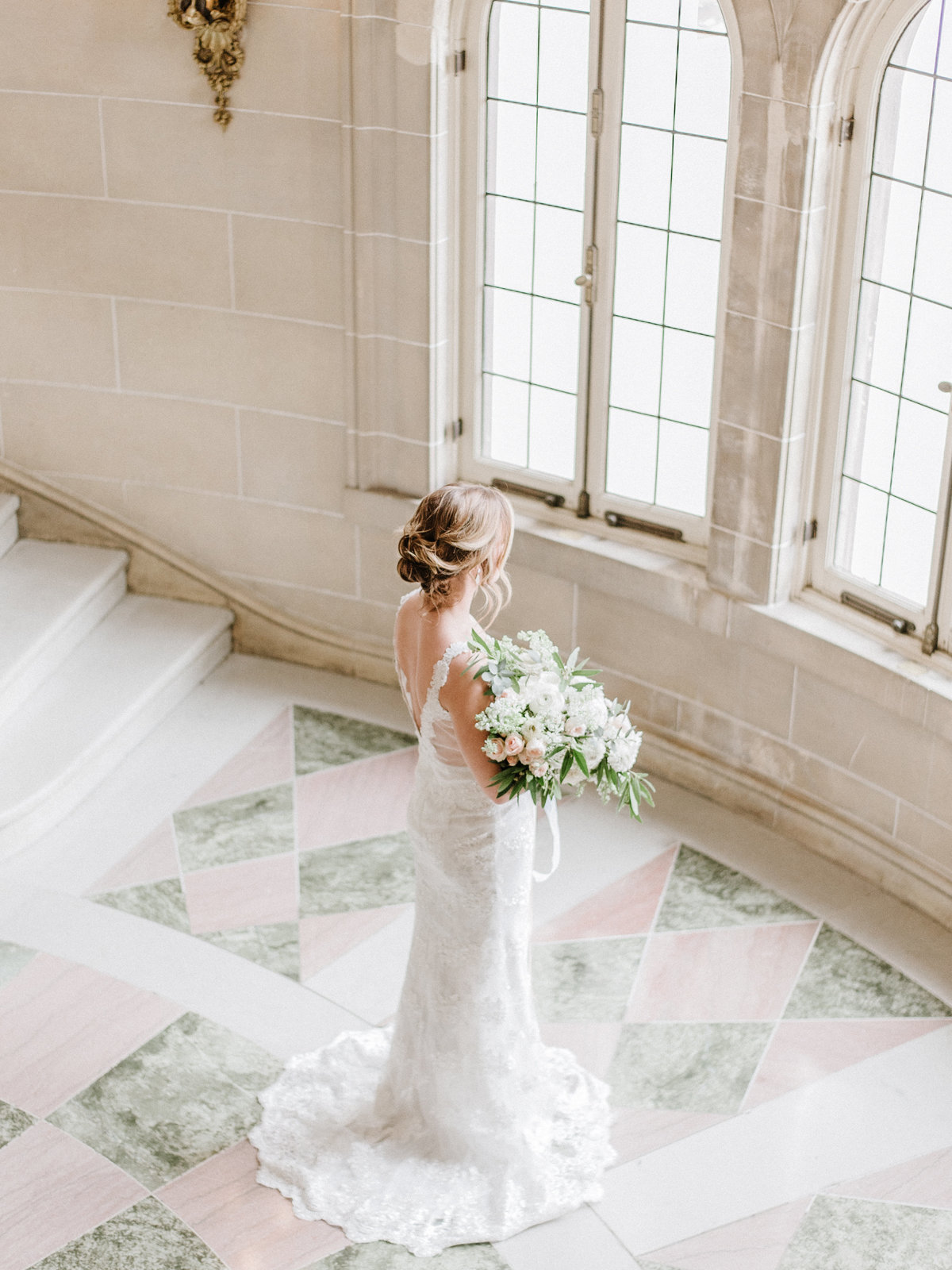bride holding flowers facing a wall of windows