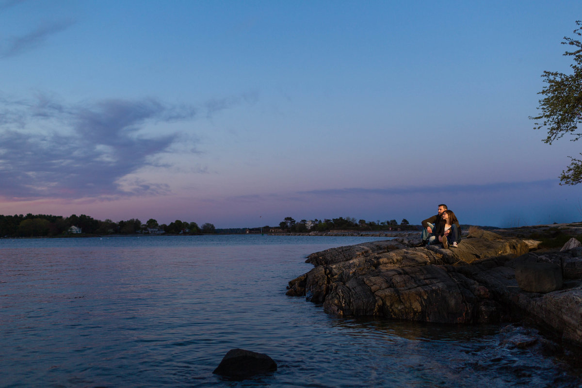 The couple sits out on the rocks for the sunset over Odiorne Point Park NH