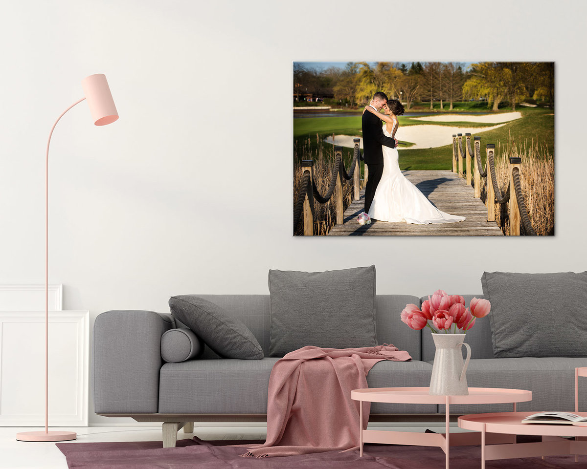 Large wedding canvas in a living room with stylish sofa and small pink table.