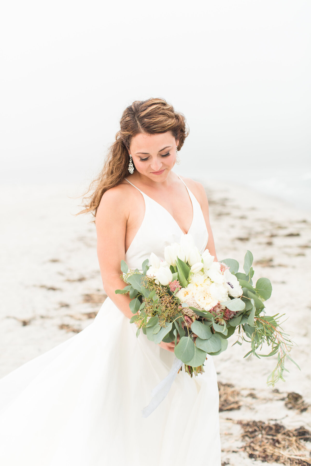 Bride looking at bouquet standing on coast of Maine