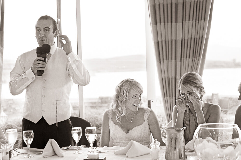 Groom in white waistcoat giving a speech at the top table in the Dingle Skellig Hotel while the bride laughs and the bridesmaid crys