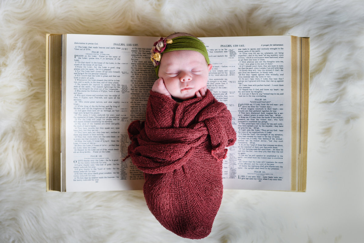 Beautiful Mississippi Newborn Photography: newborn baby girl wrapped in burgundy with floral headband laying on family Bible