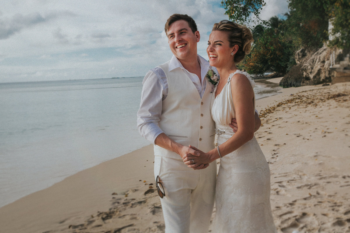 Barbados Wedding Photographer captures groom and bride stood on beach in Holetown, Barbados laughing