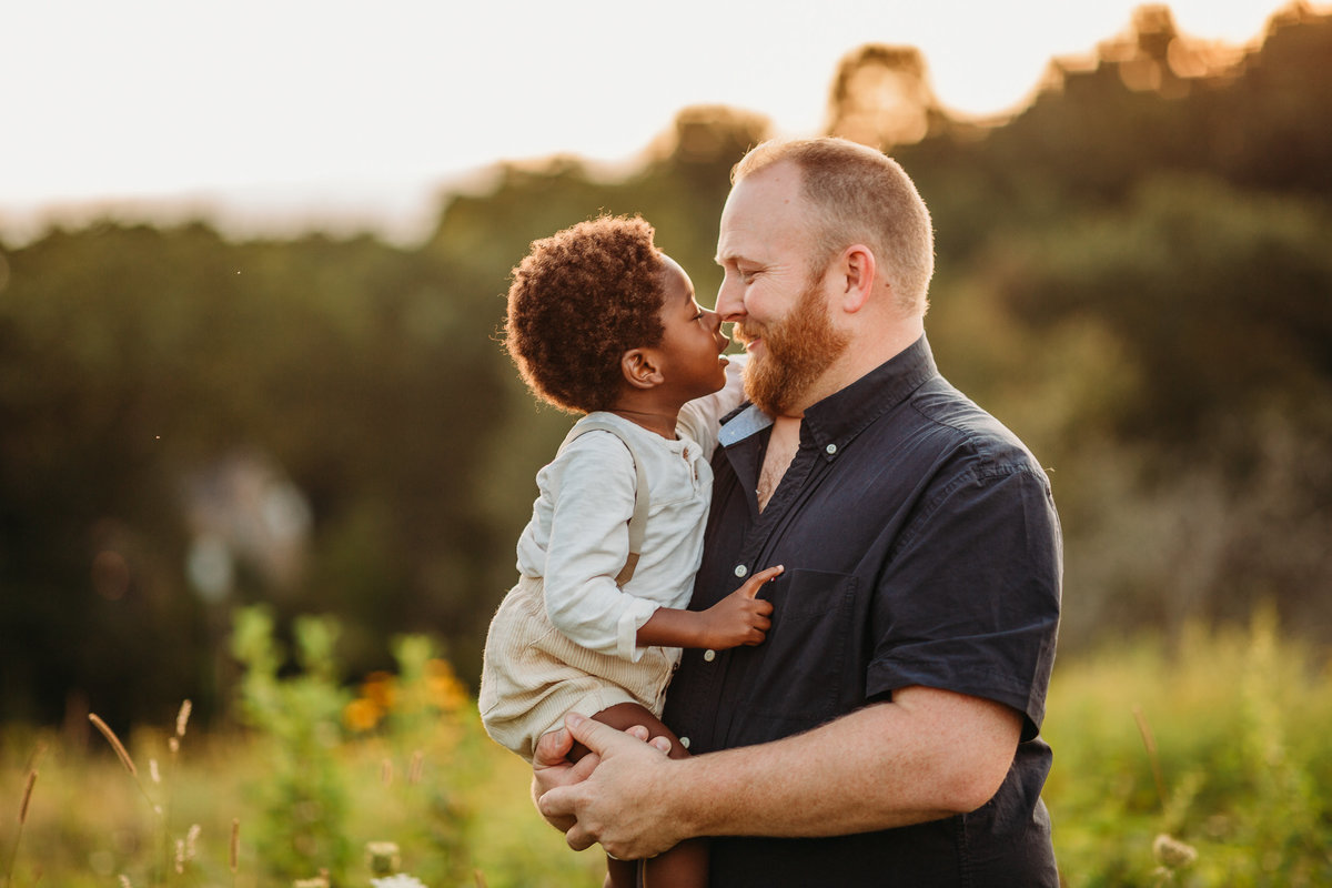 toddler son goes nose to nose with dad during family photo session in boston