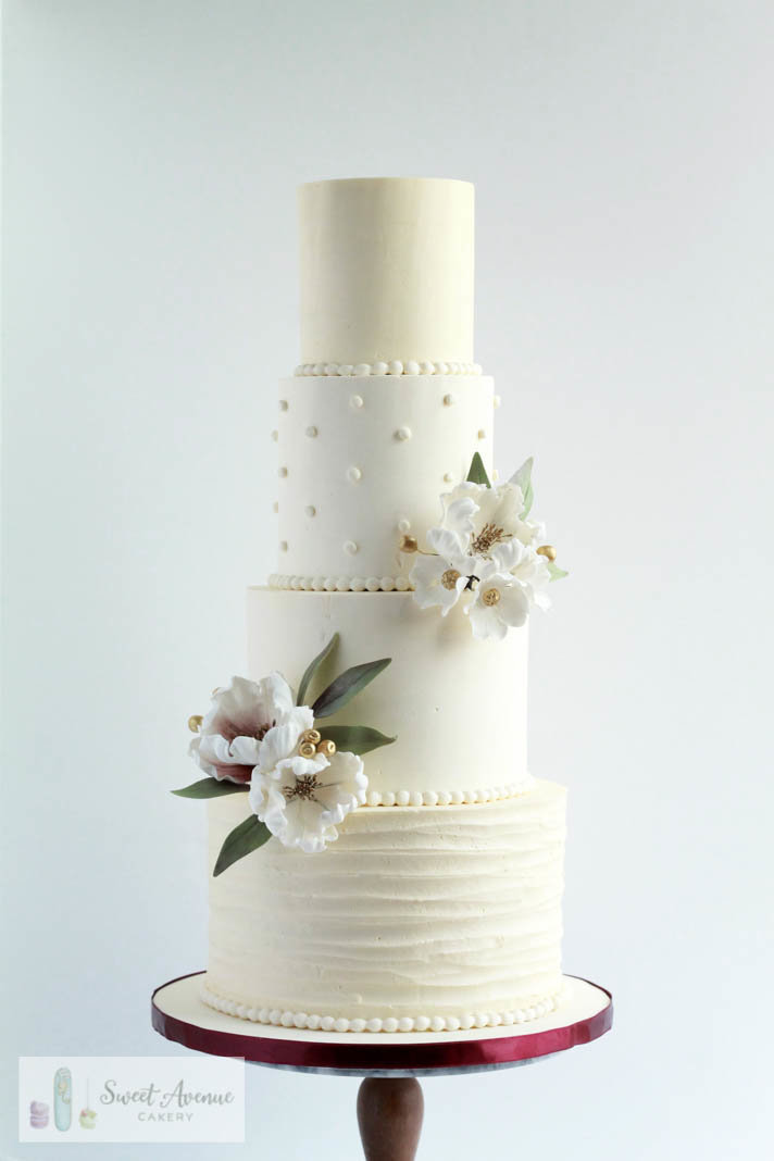 four tier textured buttercream wedding cake with flowers and burgundy details