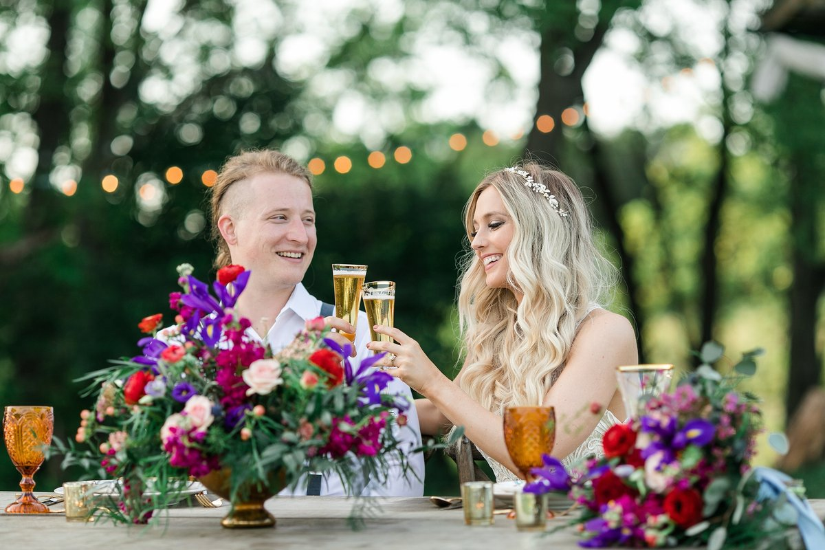 bride-groom-toasting-colorful-flowers-dinner
