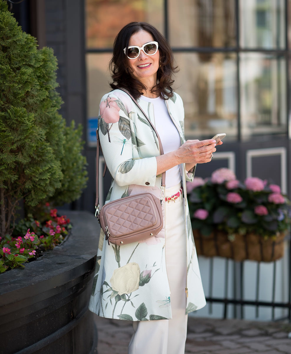 woman holding a phone standing on street modelling a handbag