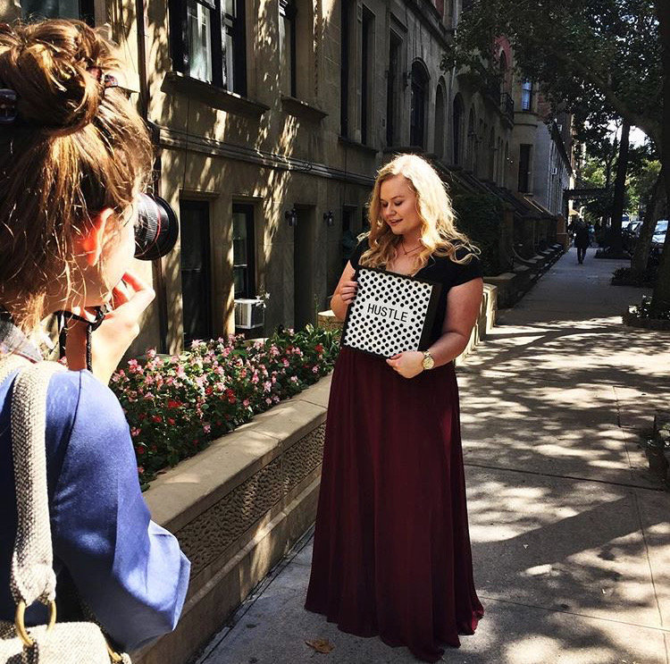"Young woman poses with ""hustle"" sign during a branding photoshoot in NYC"