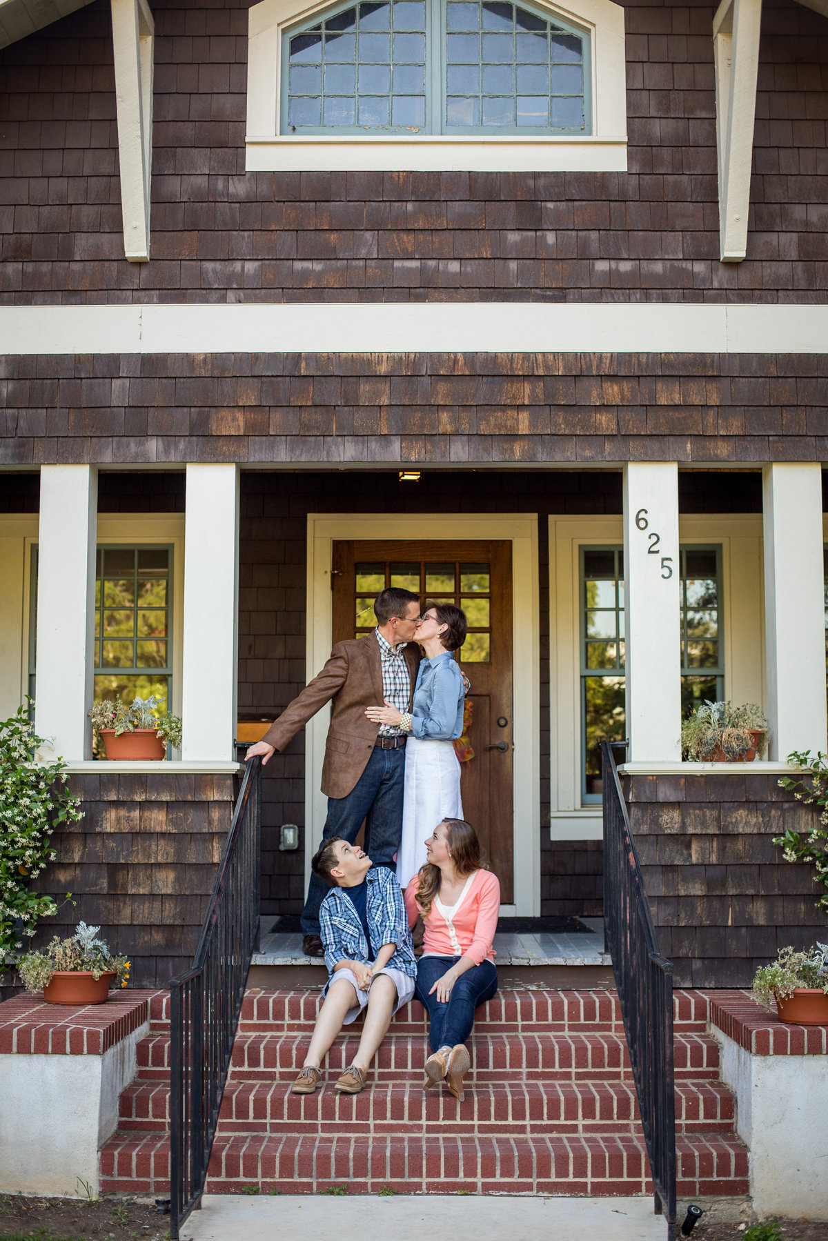 family portrait photography of mom and dad kissing on front porch and kids looking by San Antonio Photographer Expose The Heart