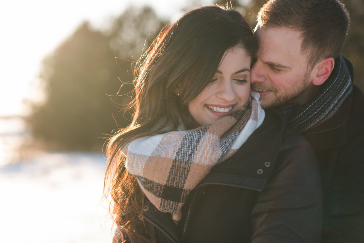 Engaged couple cuddling at sunset in winter