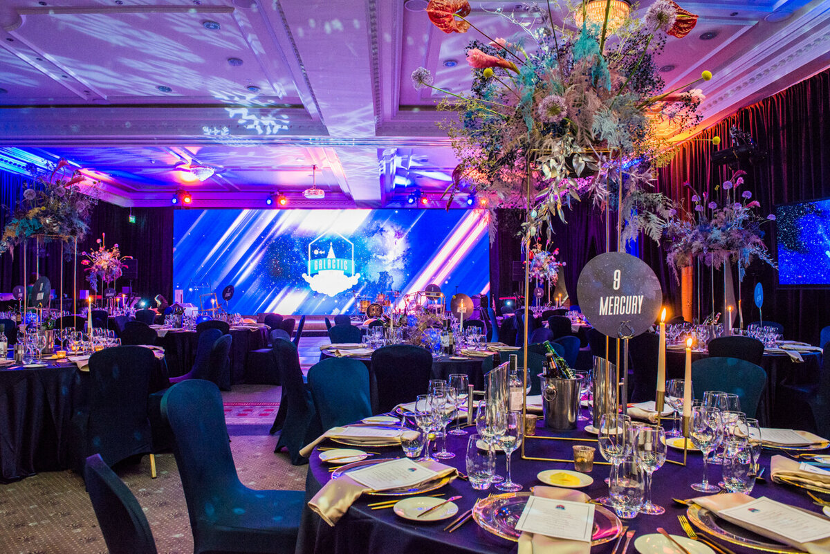decorated function room with table settings, flowers and colourful lighting